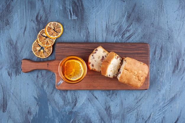 건포도와 함께 수제 케이크를 슬라이스하고 나무 커팅 보드에 차 한 잔을 놓습니다.