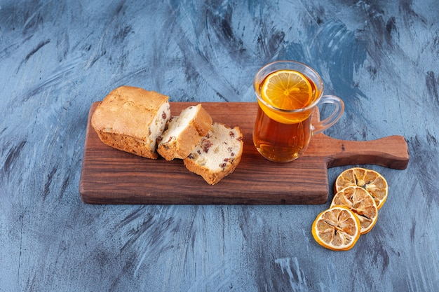 Sliced homemade cake with raisins and a glass cup of tea placed on a wooden cutting board .