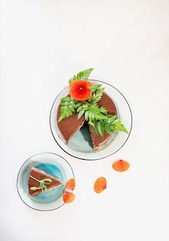 白い机の上にポピーの花と花びらで飾られたピーナッツバタークリームの層でスライスされた自家製チョコレートケーキ。上面図。