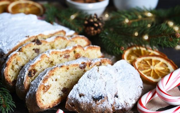 Нарезанный домашний рождественский десерт stollen с изюмом и орехами на деревенском столе с корицей. елочные ветви, выборочный фокус