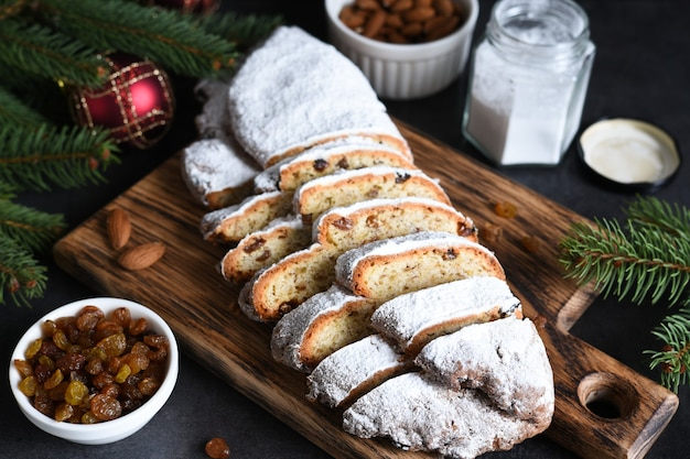 계 피와 함께 시골 풍 테이블에 건포도와 견과류와 함께 만든 크리스마스 디저트 stollen 슬라이스. 크리스마스 나무 가지, 선택적 초점