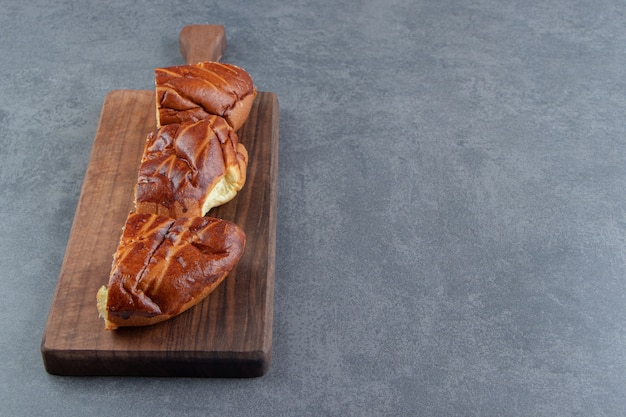 Sliced homemade fresh pastries on wooden board.