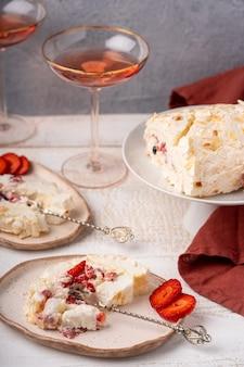 접시에 휘핑 크림, 블루 베리, 딸기와 함께 홈 메이드 머랭 롤 케이크를 슬라이스. 흰색 나무 테이블에 장미 와인 잔