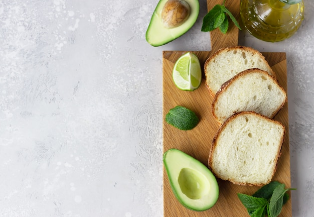 Sliced homemade no knead bread on wooden cutting board with avocado