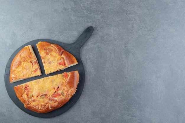 Pizza fatta in casa affettata sul tagliere nero.