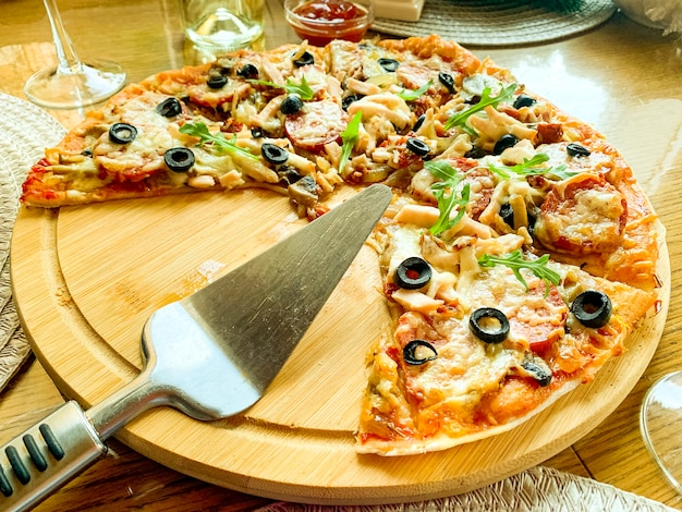 Sliced homemade pizza with salami and olives on wooden plate