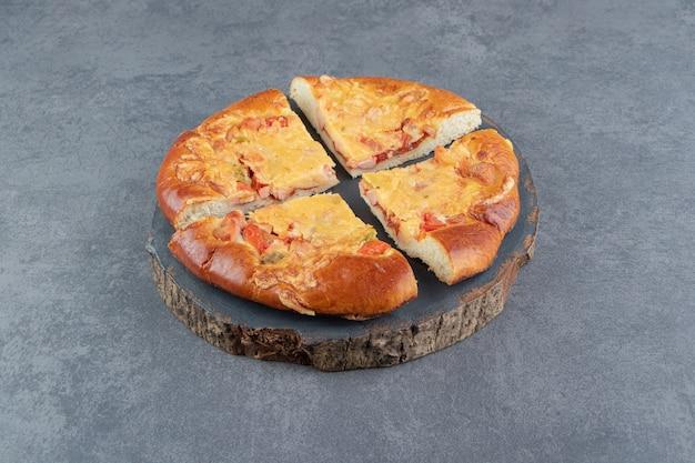Pizza fatta in casa affettata sul pezzo di legno.