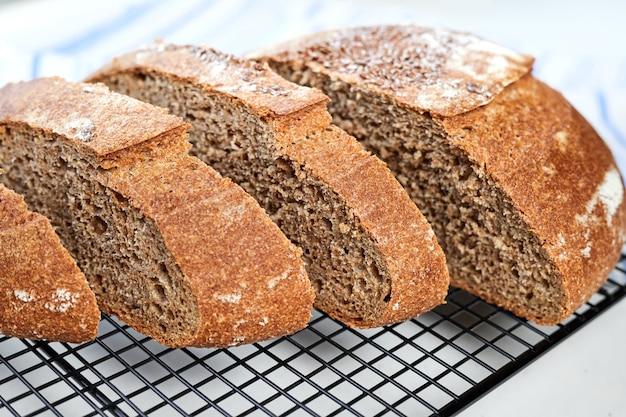 Нарезанный домашний круглый ржаной хлеб на металлической решетке с тканью