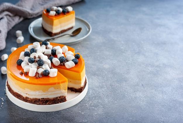 マシュマロとブルーベリーで飾られたスライスされた自家製黄色の層状ケーキ