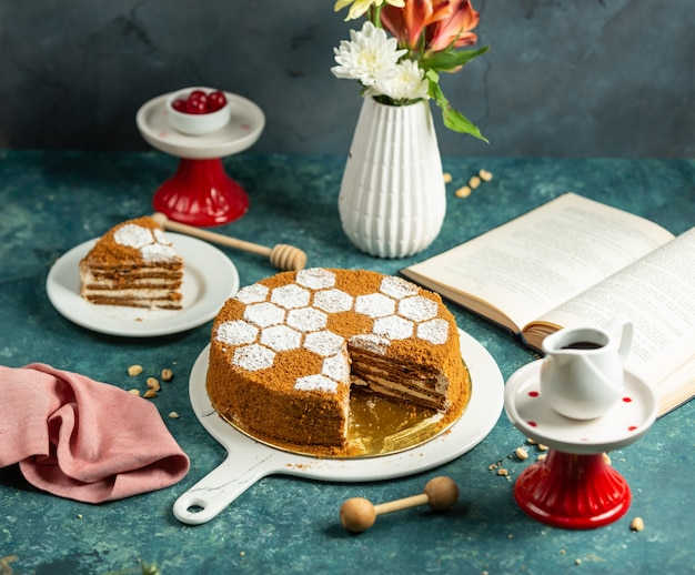 Sliced honey cake decorated with sugar powder sprinkles in bee hive shape