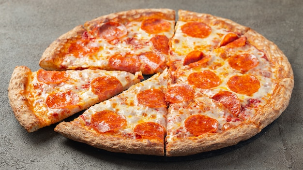 Sliced hot pepperoni pizza on a brown background.