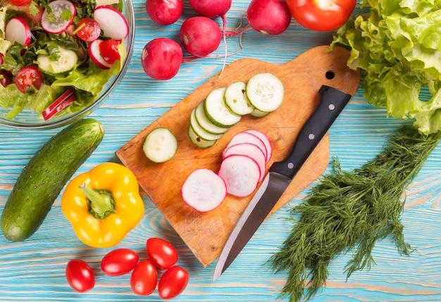 Нарезанные ингредиенты для салата на разделочной доске с ножом. свежие овощи на синем деревянном фоне. вид сверху.