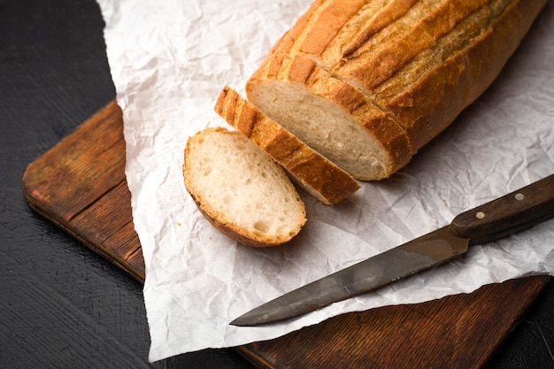 木製のまな板の上でおいしい自家製パンにスライスします。コピースペース