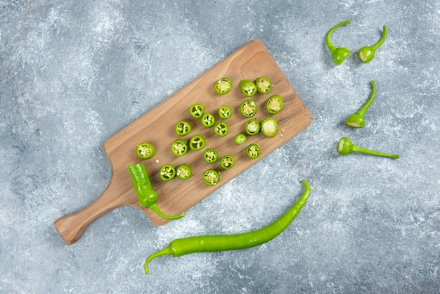 Sliced jalapeno peppers on wooden board.