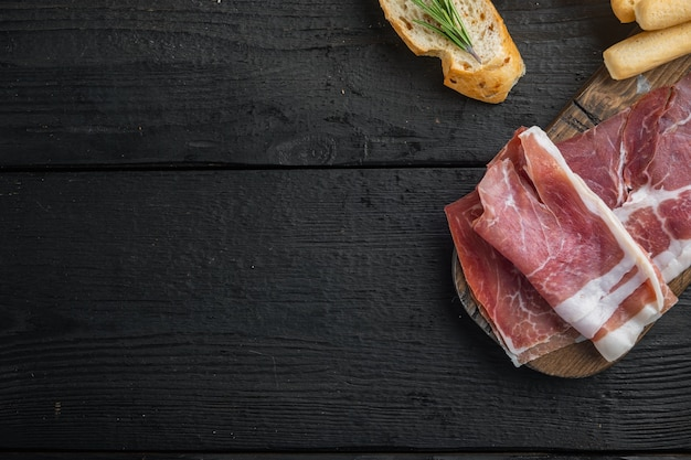 Sliced jamon set, on black wooden table, flat lay