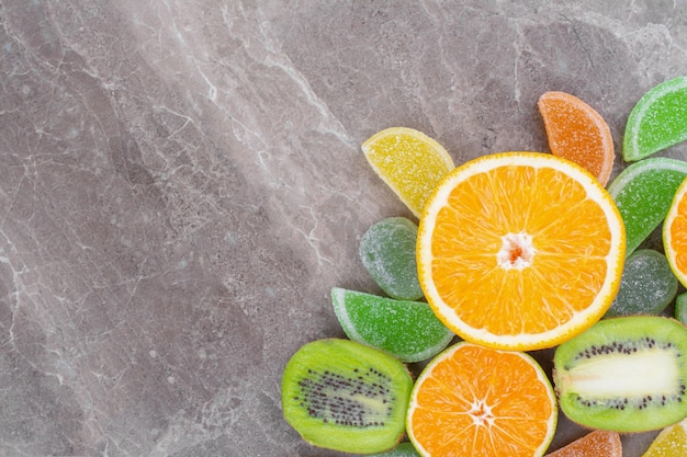 대리석 표면에 화려한 사탕과 육즙 신선한 과일을 슬라이스.