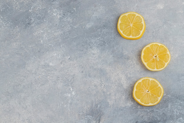 Sliced juicy fresh lemons placed on marble background.
