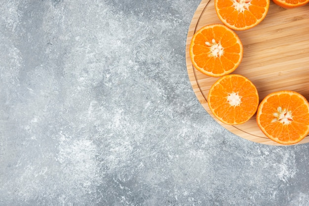 Sliced juicy fresh orange fruits in a wooden plate .