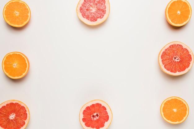 Sliced juicy grapefruit and orange on white surface
