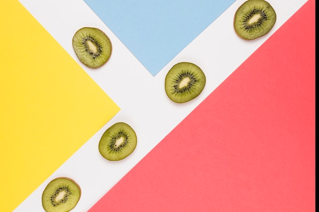 Sliced juicy kiwi on multicolored surface