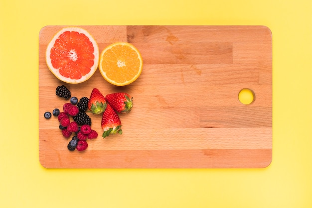 Sliced juicy orange lemon strawberry blackberry raspberry and currant on cutting board