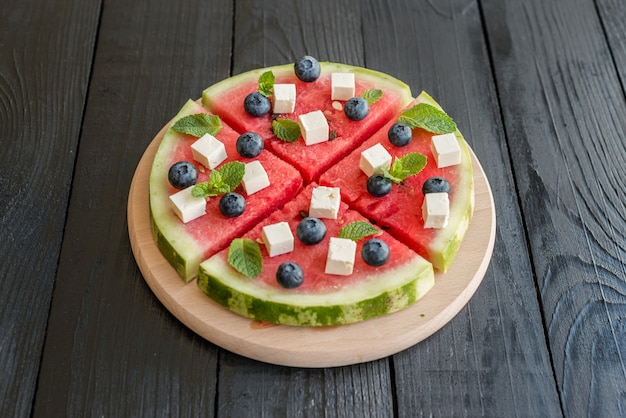 Sliced, juicy watermelon pizza with blueberries and cheese