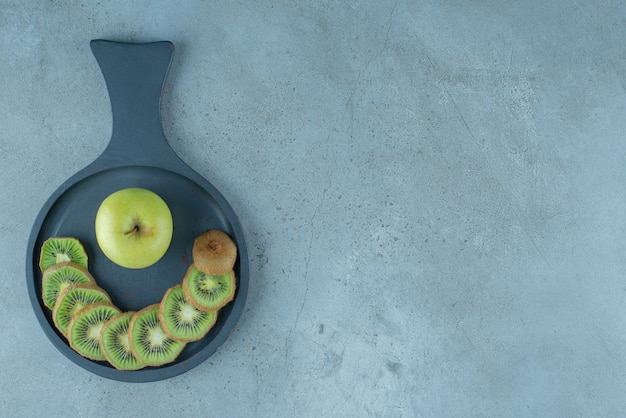 大理石の背景に、フライパンでスライスしたキウイとリンゴ。高品質の写真