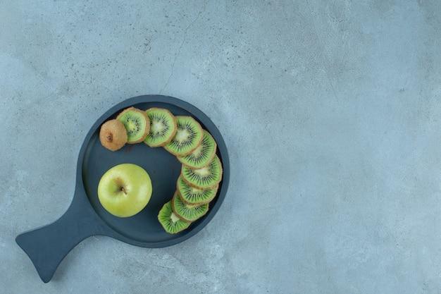 Нарезанные киви и яблоко на сковороде на мраморном столе.