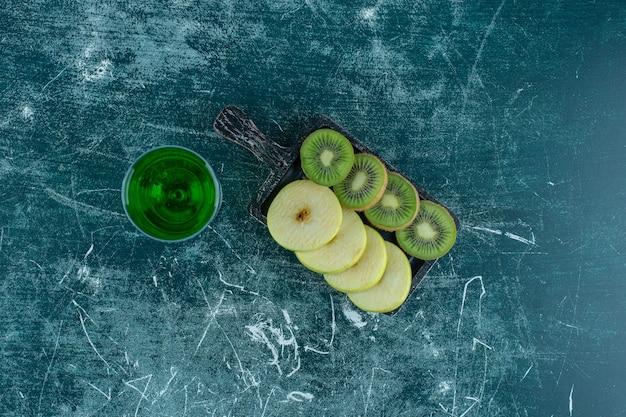 Нарезанные киви и яблоки на доске рядом с соком эстрагона на синем столе.