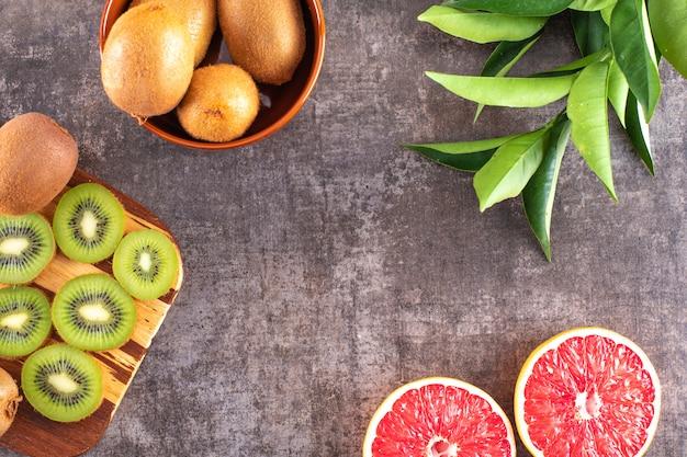 Sliced kiwi on cutting board bowl full of kiwi sliced grapefruit on grey surface
