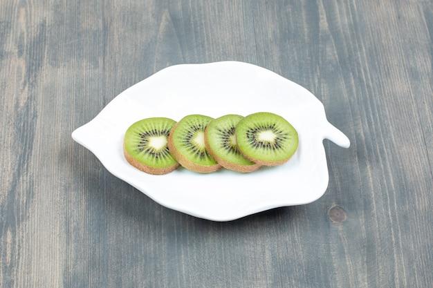 白い皿に分離されたスライスしたキウイフルーツ