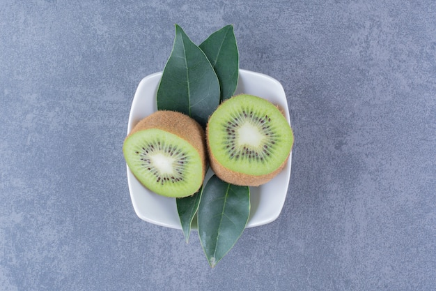 Sliced kiwi fruits in a bowl on the dark surface
