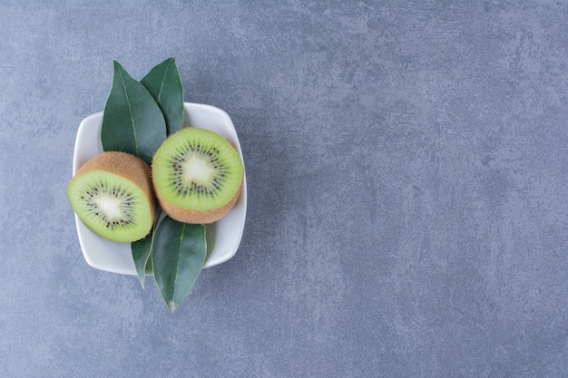 Нарезанные плоды киви в миске на темной поверхности
