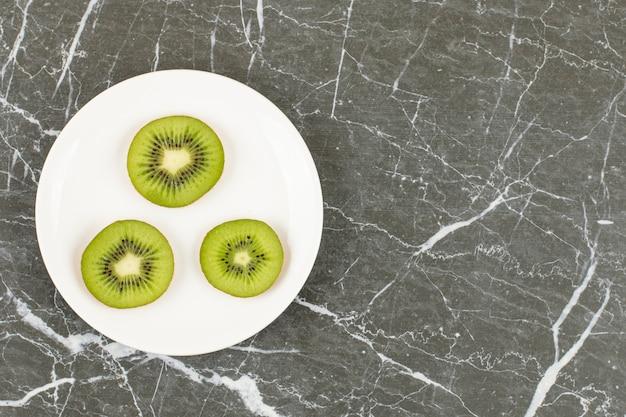 Нарезанный киви на белой тарелке над черным камнем.