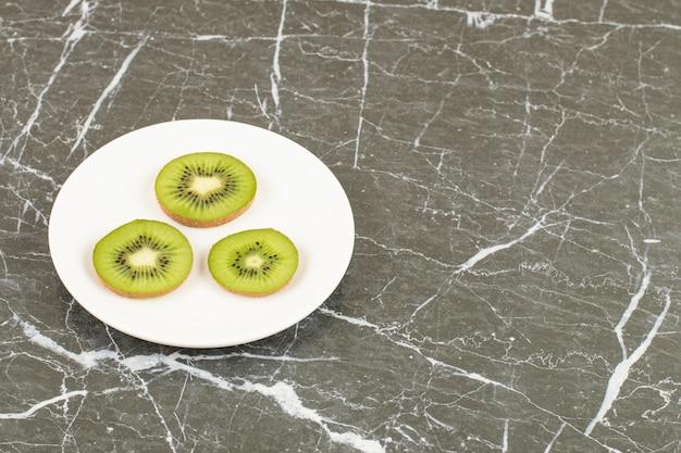 검정 위에 흰색 접시에 키위 슬라이스.