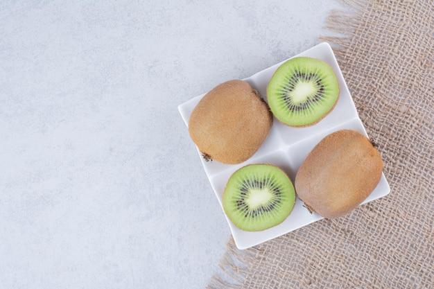 Un kiwi a fette nel piatto bianco su tela di sacco. foto di alta qualità