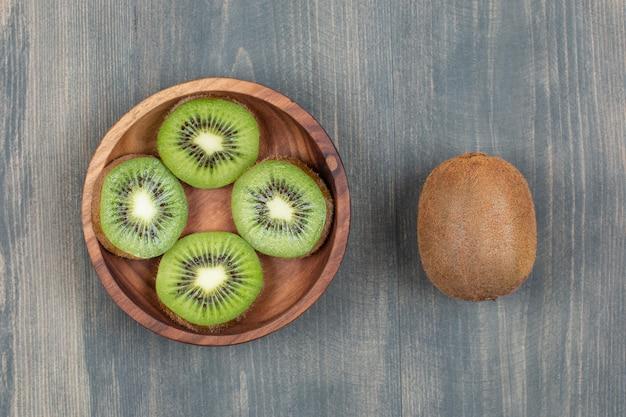 Kiwi a fette con kiwi intero su un tavolo di legno