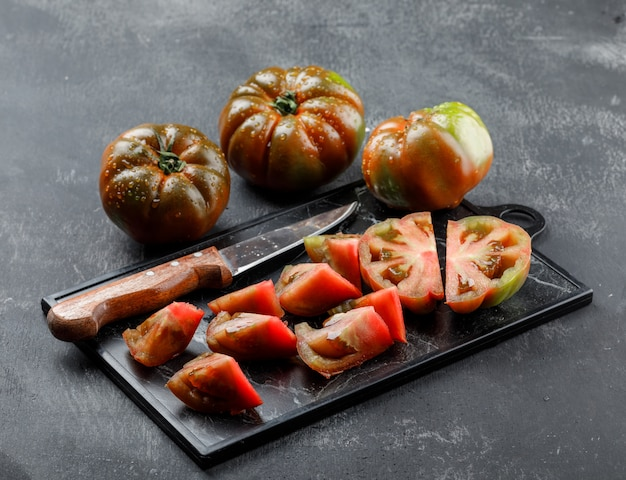 Sliced kumato tomatoes with knife on grey and cutting board wall.