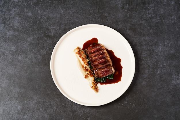 Нарезанное мясо ягненка и картофельное пюре на белой тарелке на сером столе