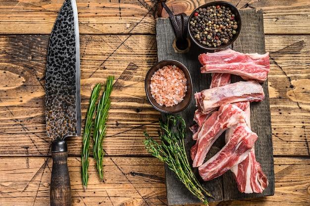 나무 커팅 보드에 양고기 짧은 여분의 허리 갈비, 생고기 슬라이스 프리미엄 사진