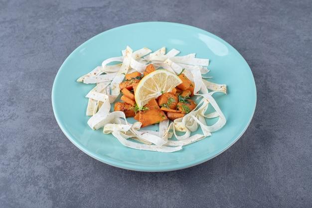 Нарезанный лаваш и запеченная морковь в тарелке на мраморной поверхности.