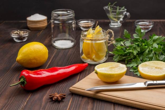 커팅 보드에 레몬과 칼을 슬라이스. 항아리에 레몬. 칠리 페 퍼, 전체 레몬 및 소금 테이블에. 면역 강화의 천연 원천.