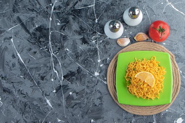 Нарезанный лимон и лапша на тарелке на подставке рядом с помидорами, солью и чесноком на мраморном фоне.