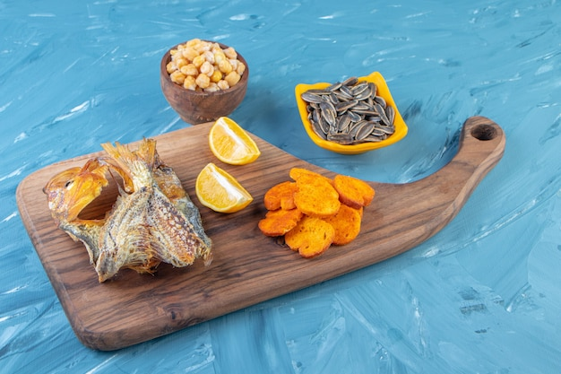 Sliced lemon, bread chips and dried fish on a cutting board , on the blue surface.
