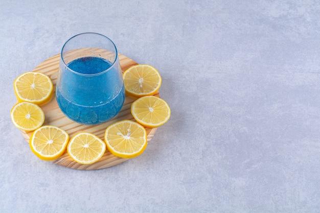 Limone a fette accanto a un bicchiere di frullato blu su un piatto di legno, sullo sfondo di marmo.