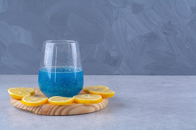 Sliced lemon next to a glass of blue smoothie on a wooden plate , on the marble table.