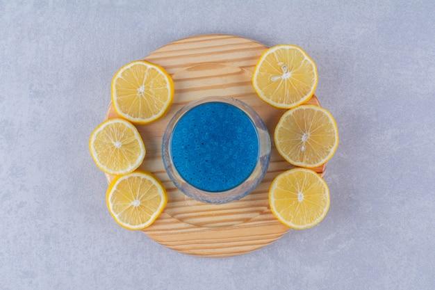 대리석 테이블에 있는 나무 접시에 있는 파란색 스무디 한 잔 옆에 얇게 썬 레몬.