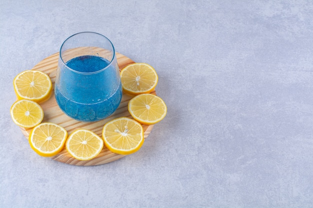 대리석 배경에 있는 나무 접시에 있는 파란색 스무디 한 잔 옆에 얇게 썬 레몬.