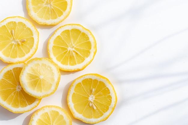Нарезанный лимон на белом фоне с солнечным светом и тенями