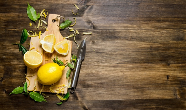 Нарезанный лимон на доске с листьями. на деревянном столе. свободное место для текста. вид сверху